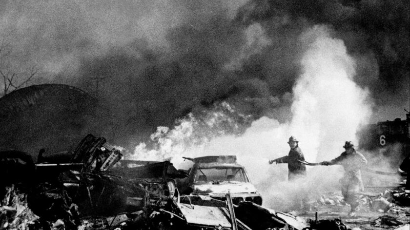 Firemen pour water on flaming wreckage of American Airlines Flight 191 DC-10 aircraft shortly after