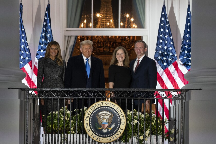 President Donald Trump, first lady Melania Trump, and Amy Coney Barrett and her husband Jesse stand on the Blue Room Balcony after Supreme Court Justice Clarence Thomas administered the Constitutional Oath to her on the South Lawn of the White House White House in Washington, Monday, Oct. 26, 2020. Barrett was confirmed to be a Supreme Court justice by the Senate earlier in the evening. (AP Photo/Alex Brandon)
