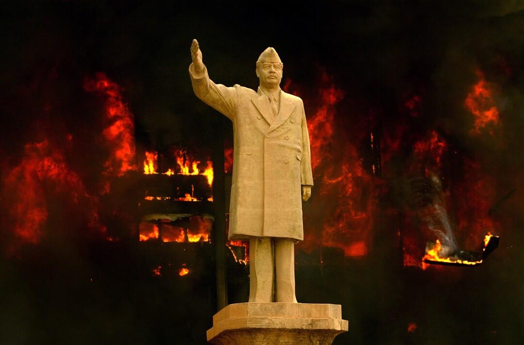 مجسمه صدام حسین با دست بالا در مقابل ساختمان سوخته
