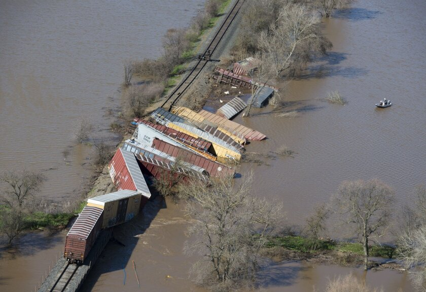Cars from a freight train derailment lie along the track and in the water of the swollen Cosumnes River on Saturday, near Elk Grove, Calif.