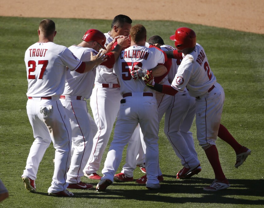 Angels third baseman Taylor Featherston is mobbed by his teammates after hitting a walk-off single in the 13th inning against the Houston Astros. The Angels beat the Astros, 2-1.