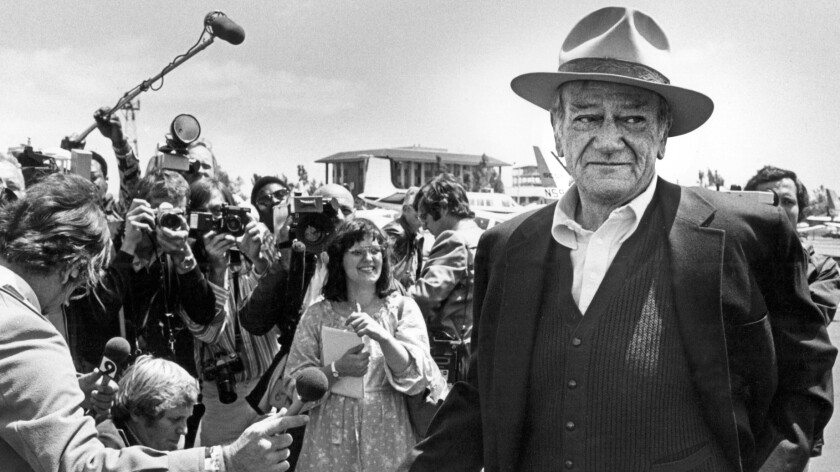 John Wayne chats with reporters in 1978 at the Orange County Airport, which became his namesake a year later.