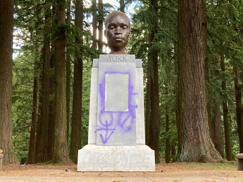 This Thursday, June 10, 2021 photo shows a statue commemorating York, an enslaved Black member of the Lewis and Clark Expedition, after being defaced in Portland, Ore. (Catalina Gaitán/The Oregonian via AP)