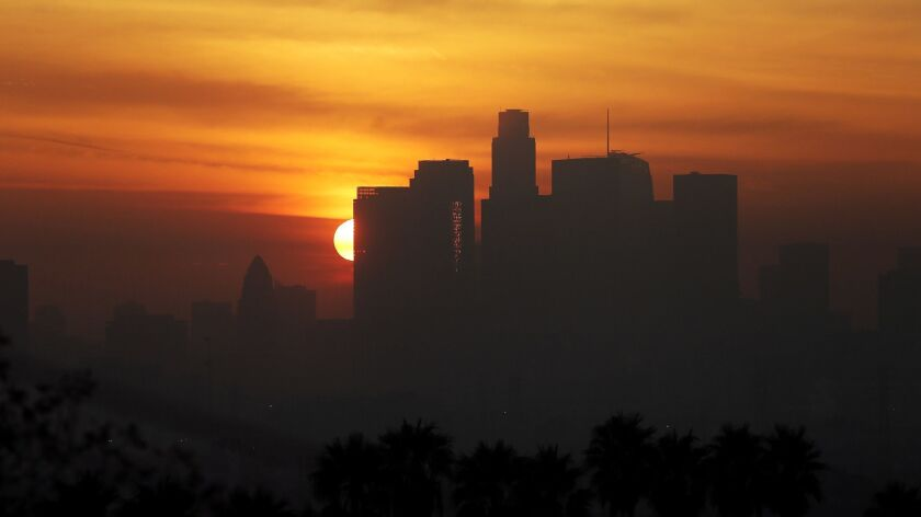 The sun sets behind the downtown Los Angeles skyline on Dec. 14, 2016.