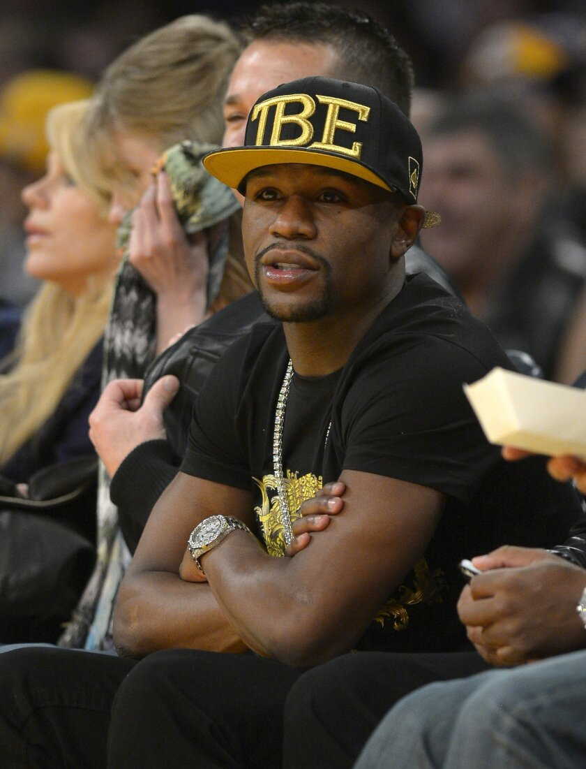 FILE - In this Nov. 24, 2013, file photo, Boxer Floyd Mayweather Jr. watches the Los Angeles Lakers play the Sacramento Kings during the first half of an NBA basketball game in Los Angeles. If Donald Sterling is compelled to sell the Los Angeles Clippers, the list of potential buyers will have more