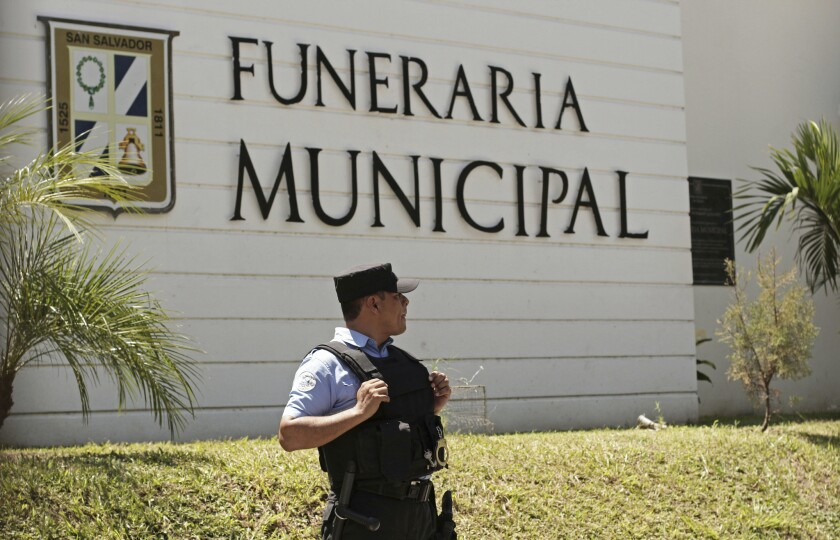 A police officer stands outside the municipal funeral home at La Bermeja cemetery, where the bodies of Oscar Alberto Martinez Ramirez, 25, and daughter Angie Valeria, nearly 2, arrived in San Salvador.