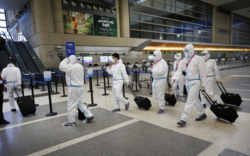 The crew for a Hainan Airlines flight walks through the Tom Bradley International Terminal at Los Angeles International Airport, which is now requiring travelers to wear face coverings during the coronavirus outbreak.