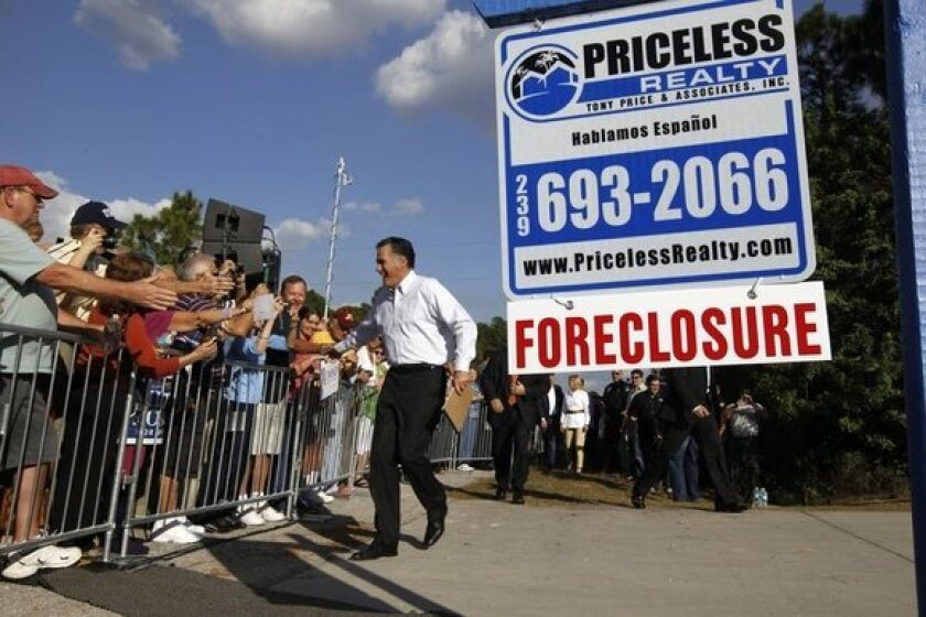 Mitt Romney greets the crowd as he arrives for a campaign rally in front of a foreclosed home in Lehigh Acres, Fla.