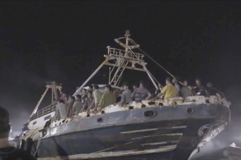 In this frame taken from video, a fishing boat with migrants is docked at the port of the Sicilian island of Lampedusa, southern Italy, late Monday, Sept. 27, 2021. A rusty, overloaded fishing boat carrying nearly 700 migrants arrived at an Italian island port amid fresh diplomatic efforts by Mediterranean governments to seek more European help in handling migrant flows. (AP Photo/Mauro Buccarello)