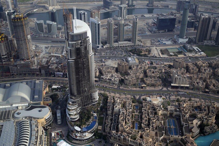 In this Sunday, Jan. 10, 2016 photo, the burned hulk of The Address Downtown is seen in Dubai, United Arab Emirates. Skyscraper fires like the blaze that struck the 63-story luxury hotel in Dubai on New Year's Eve, swiftly turning it into a towering inferno, are not that rare. The New Year's Eve tower fire in Dubai has raised new issues about the safety of exterior sidings put on high-rise buildings in the United Arab Emirates and around the world.