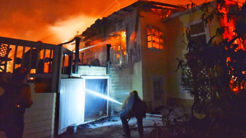 In this July 6 photo provided by the Santa Barbara County Fire Department, firefighters put water on flames at a Goleta home. With the Holiday fire 85% contained, one resident, John Davis, returned to find his house (not pictured) was still standing.