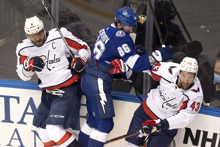 Washington Capitals left wing Alex Ovechkin (8) and right wing Tom Wilson (43) team up to take Tampa Bay Lightning right wing Nikita Kucherov (86) into the boards during the first period of an NHL Stanley Cup playoff hockey game in Toronto, Monday, Aug. 3, 2020. (Frank Gunn/The Canadian Press via AP)