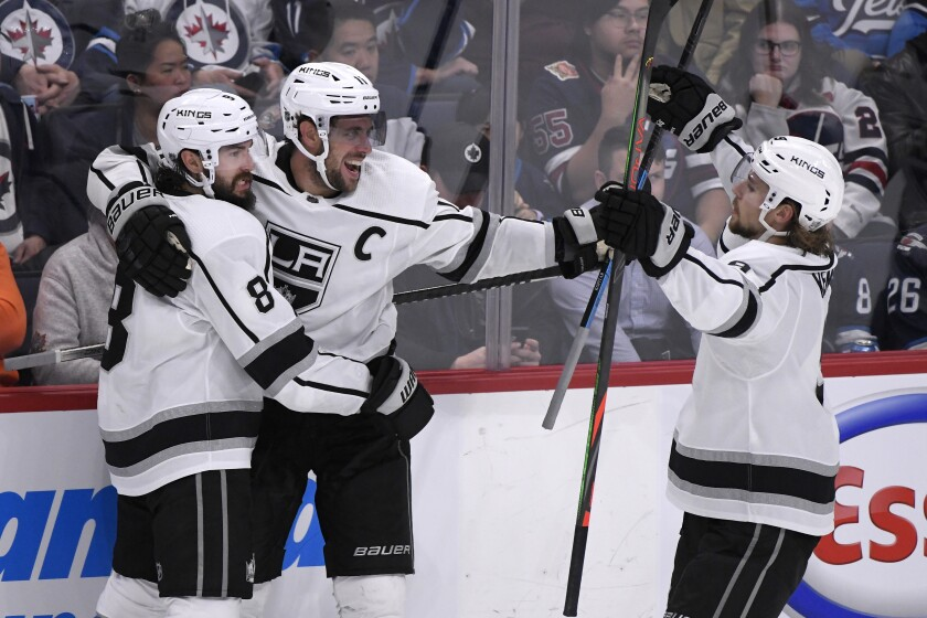 Kings forward Anze Kopitar, center, celebrates with teammates Drew Doughty, left, and Adrian Kempe after scoring a goal.