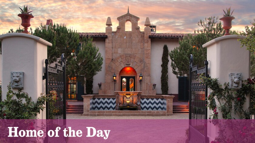 Iron gates open to a motor court marked by an elaborate fountain at the front of the Santa Barbara estate.