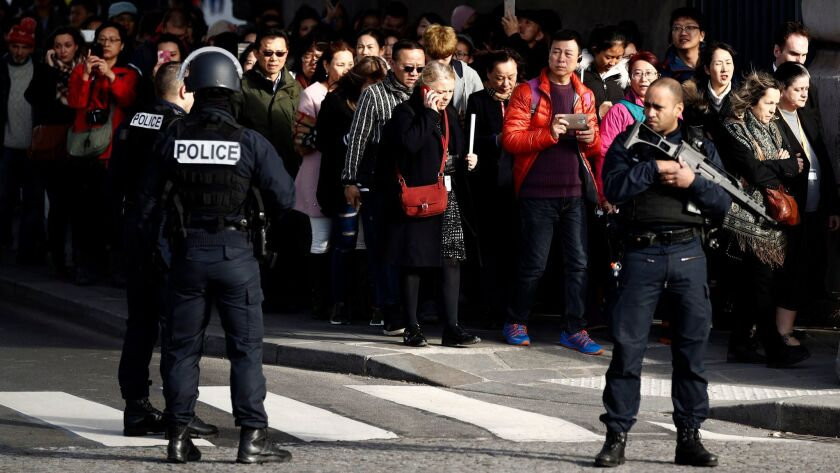 """People are evacuated by police officers from the Pyramid of the Louvre Museum, close to the Carrousel du Louvre, where a French soldier opened fire after an attempted machete attack by a man allegedly shouting """"Allahu Akbar,"""" in Paris."""