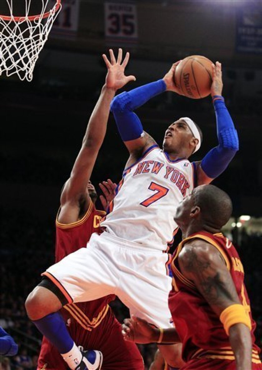 New York Knicks' Carmelo Anthony (7) shoots over Cleveland Cavaliers' Antawn Jamison, right, and Samardo Samuels, left, during the first half of an NBA basketball game, Saturday, March 31, 2012, in New York. (AP Photo/Frank Franklin II)