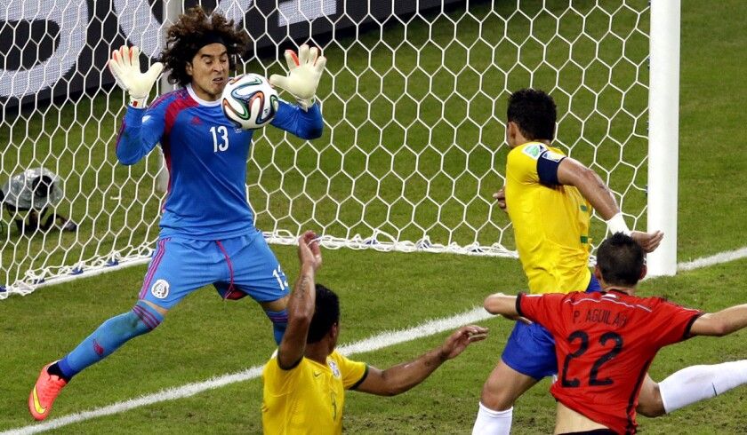 Mexico goalkeeper Guillermo Ochoa blocks a header by Brazil's Thiago Silva late in the second half of their World Cup Group A game Tuesday at Arena Castelao in Fortaleza, Brazil.