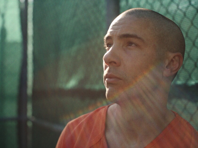 """Tahar Rahim looks to the sky in the prison yard in """"The Mauritanian."""""""