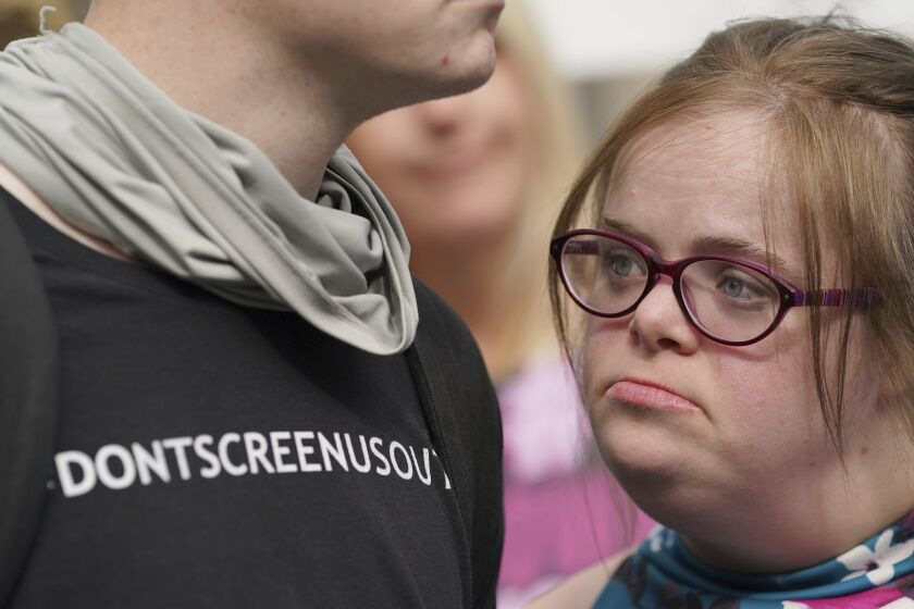 """Campaigner Heidi Crowter looks on after speaking to the media after her court case, outside the High Court in London, Thursday, Sept. 23, 2021. A woman with Down's syndrome has lost a court challenge against the British government over a law allowing the abortion up until birth of a foetus with the condition. Heidi Crowter, 26, and two others argued that part of the Abortion Act is discriminatory. Abortions in England, Wales and Scotland are allowed up till 24 weeks of pregnancy, but terminations can be allowed up until birth if there is """"a substantial risk"""" that if the child were born it would suffer from serious abnormalities. (Gareth Fuller/PA via AP)"""
