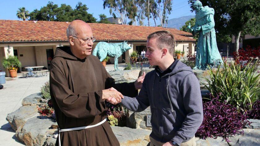 St. Francis High School President Father Tony Marti congratulates Danny Bozanic, 17, a junior at St.