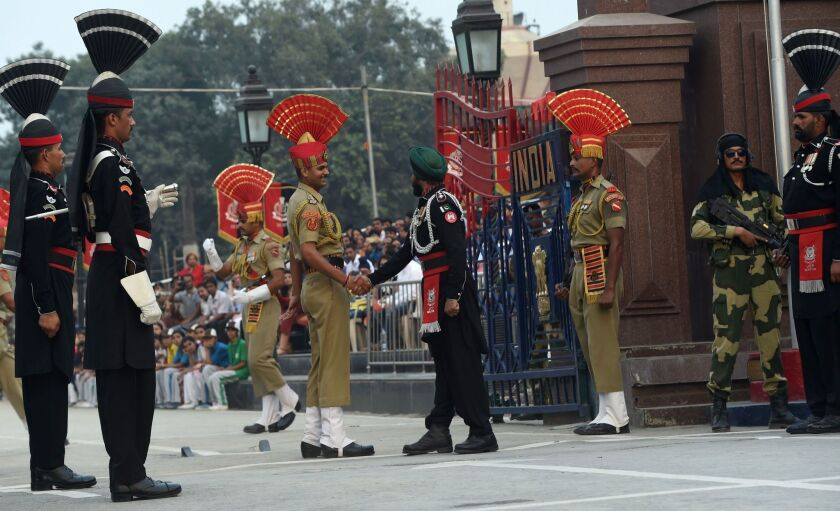 A Pakistani Ranger, right, and an Indian Border Security Force soldier shake hands during a flag ceremony at the India-Pakistan Wagah Border Post on Oct. 20, 2016.