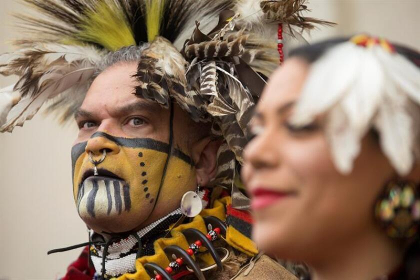 Keith Anderson (i), miembro de la Nación India Nansemond y director del grupo de baile nativo americano ''Cielo rojo torcido'', participa junto a Nikki Bass (d), también miembro del grupo de baile, en una manifestación este viernes en Washington (Estados Unidos). EFE