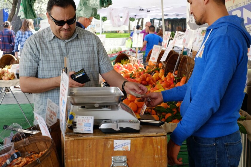 In this Friday, Feb. 6, 2015 photo, a shopper pays for his produce at a farmers market in downtown Los Angeles. The Conference Board releases its February index on U.S. consumer confidence on Tuesday, Feb. 24, 2015. (AP Photo/Richard Vogel)