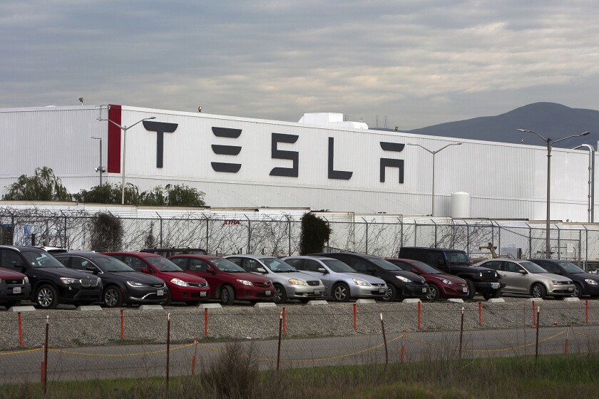 A row of cars parked in front of a white building marked TESLA.