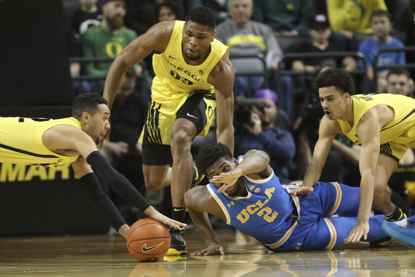 UCLA's Cody Riley battles with Oregon's Anthony Mathis, left, and Francis Okoro, for a loose ball during the first half of a game Jan. 26.