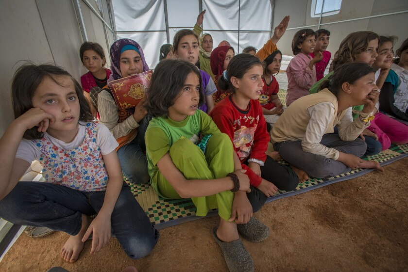 Children in a makeshift school run by the IRC at the Karameh displacement camp in Syria's Idlib Governorate.