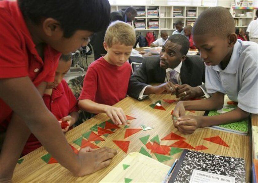 """Hayward Jean, 27, center, works with his fourth grade single gender students during a math lesson on patterns Tuesday, Sept. 29, 2009, at Marshall Elementary School in Orangeburg, S. C. Jean is a graduate of the Mentors Instructing Students Toward Effective Role Models called """"Call Me Mister """" from Claflin University. (AP Photo/Mary Ann Chastain)"""