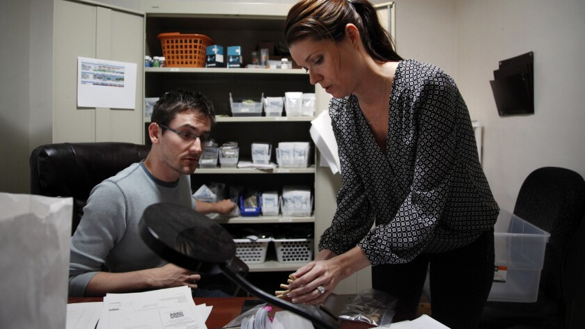 David Neale and Jennifer Costa pack a patient's order of medical marijuana in the offices of delivery service Speed Weed, headquartered in Agoura Hills.