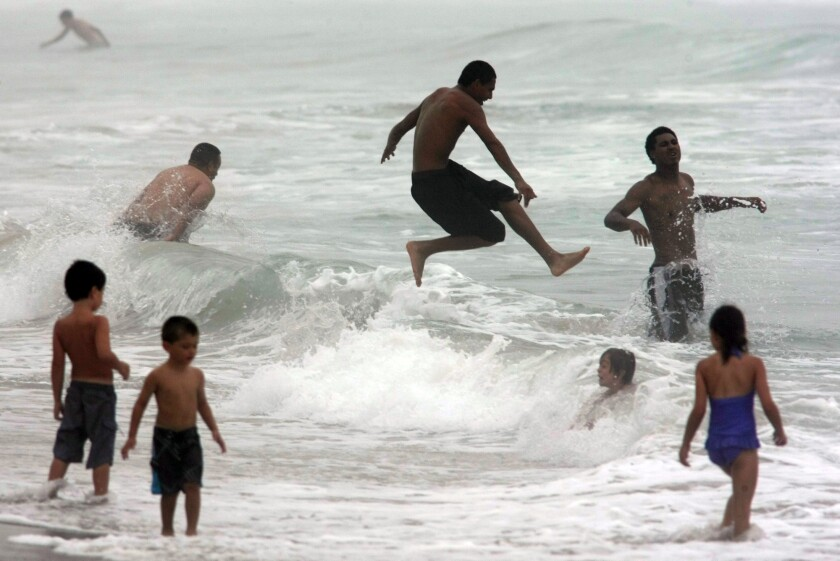 Beachgoers try to stay cool Thursday afternoon while a marine layer continues to hover over Zuma Beach in Malibu.