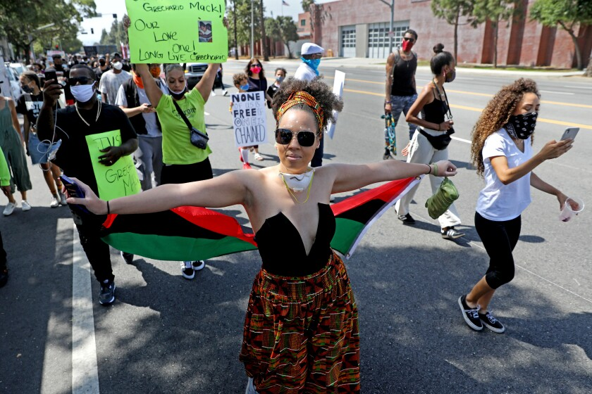 People walk along Martin Luther King Boulevard in Los Angeles on June 19, 2020