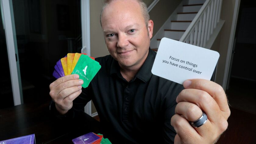 Portrait of Jeff Holland displaying one of his Coping Cards with a motivational message.