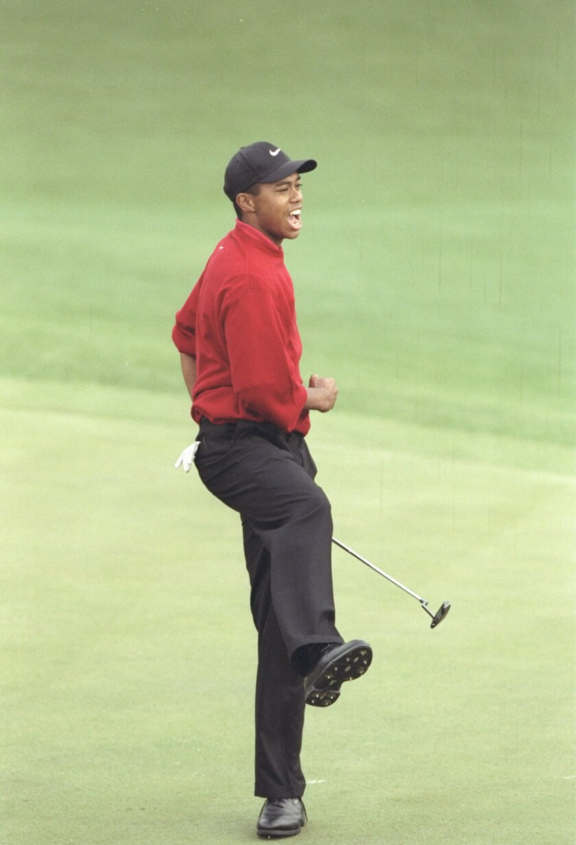 Tiger Woods celebrates after making a par putt to win the 1997 Masters Tournament.