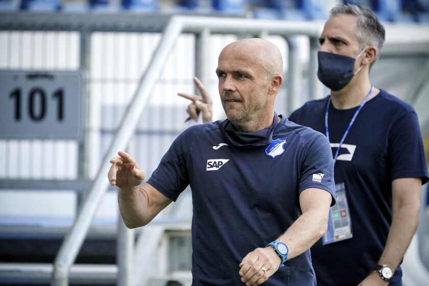 Hoffenheim head coach Alfred Schreuder, foreground, arrives for the German Bundesliga soccer match between TSG 1899 Hoffenheim and 1. FC Cologne in Sinsheim, Germany, Wednesday, May 27, 2020. The German Bundesliga is the world's first major soccer league to resume after a two-month suspension because of the coronavirus pandemic. (Ronald Wittek/Pool via AP)