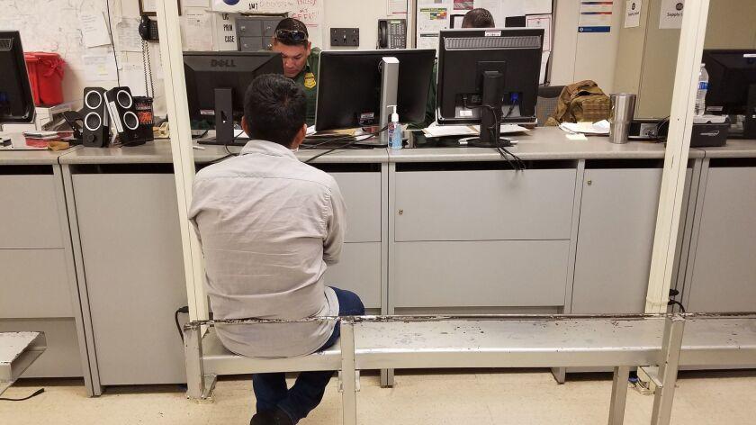 PRESIDIO TEXAS DECEMBER 13, 2017 -- Border Patrol agents in Presidio, Texas, process a migrant, one