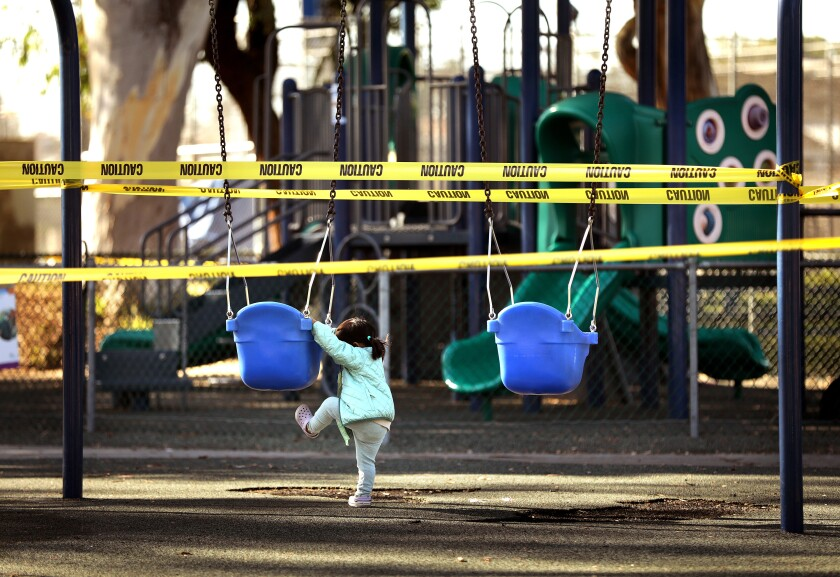 A toddler tries to climb onto a swing in a closed-off playground