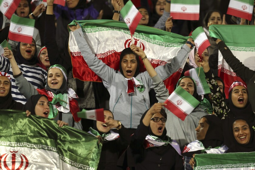 Iranian women cheer in October 2018 as they wave their country's flag after authorities, in a rare move, allowed a select group of women into Tehran's Azadi Stadium to watch a friendly soccer match between Iran and Bolivia.
