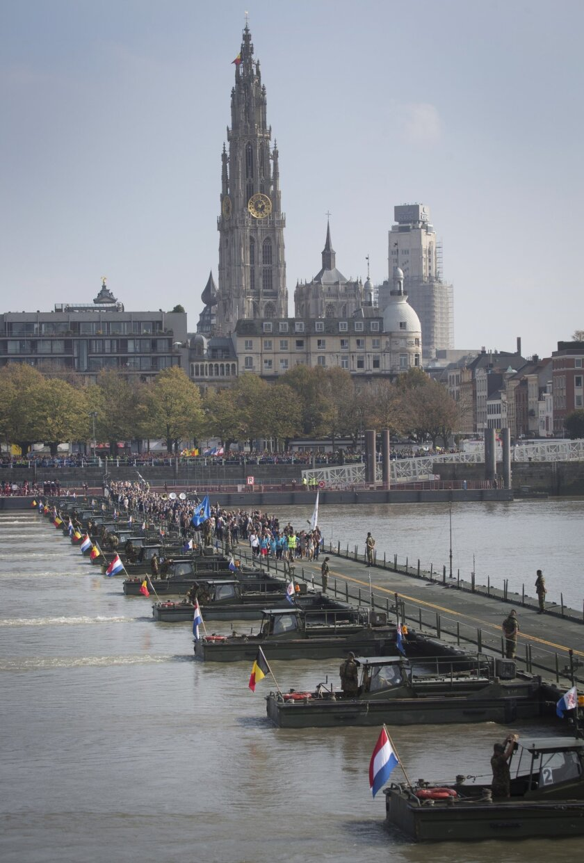 People cross over a floating pontoon bridge on the River Scheldt in Antwerp, Belgium on Friday, Oct. 3, 2014. Antwerp opened it's World War I Centenary program with the pontoon bridge and will allow the general public to cross it for two days. The pontoon bridge is an actual reconstruction of the original that spanned the River Scheldt at the start of the war in 1914 and played a major role in the defense of Antwerp. It was used by the Belgian army under King Albert I as well as the British Expeditionary Force under Winston Churchill. (AP Photo/Virginia Mayo)