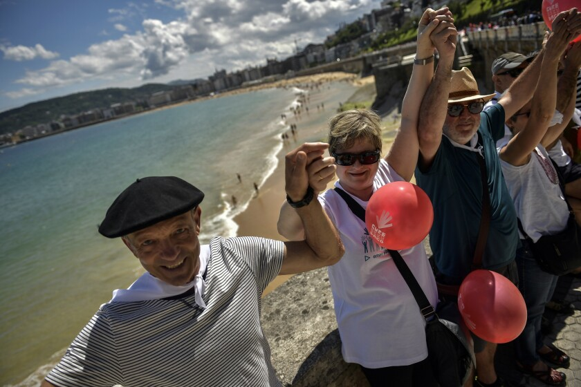People gather along La Concha beach, as thousands independence of demonstrators make a human chain c
