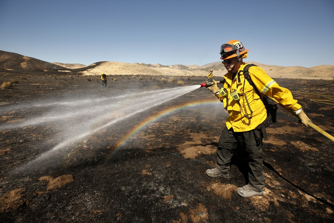 Water from a firefighter's hose creates a rainbow in a burned area