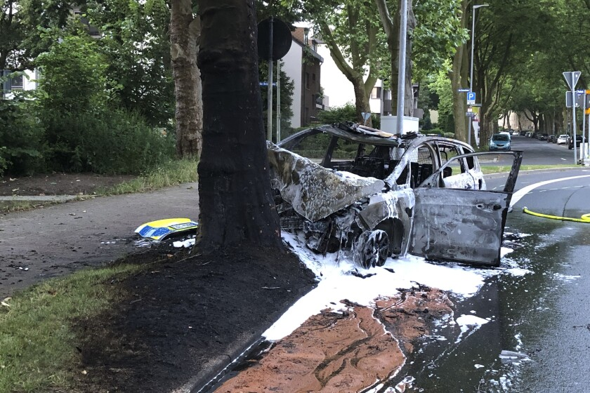 This by Police Bochum provided photo shows a destroyed police car at a tree in Bochum, Germany, Friday morning, June 25, 2021. German police say four students walking home from their high school graduation ceremony helped rescue two police officers from a burning patrol car in the early hours of Friday. Police in the western city of Bochum said Friday that the 24 and 30-year-old officers were on their way to a reported burglary when their vehicle crashed into a tree and burst into flames. (Police Bochum via AP)