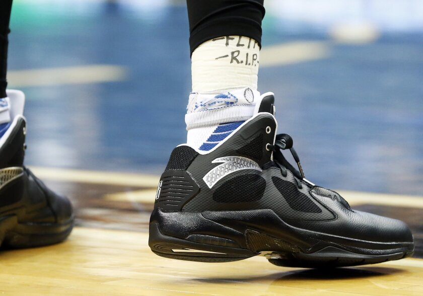 The sock of Minnesota Timberwolves' Kevin Garnett honor the late Timberwolves head coach Flip Saunders, who died Oct. 25, 2015, during an NBA basketball game against the Portland Trail Blazers, Monday, Nov. 2, 2015, in Minneapolis. The Trail Blazers won 106-101. (AP Photo/Jim Mone)