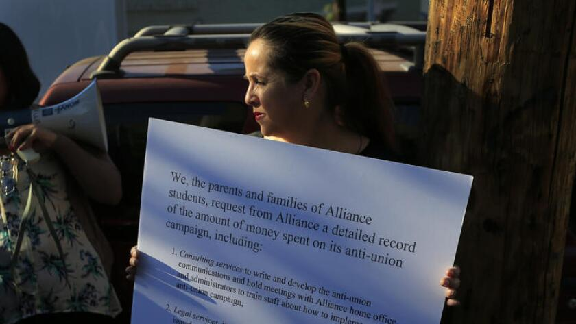 Maria Esparza, de Huntington Park, en el exterior de Alliance Gertz-Ressler Academy High School en Los Ángeles. Esparza sostiene un cartel que detalla las preocupaciones de los padres acerca de la manipulación de la sindicalización (Allen J. Schaben/Los Angeles Times).