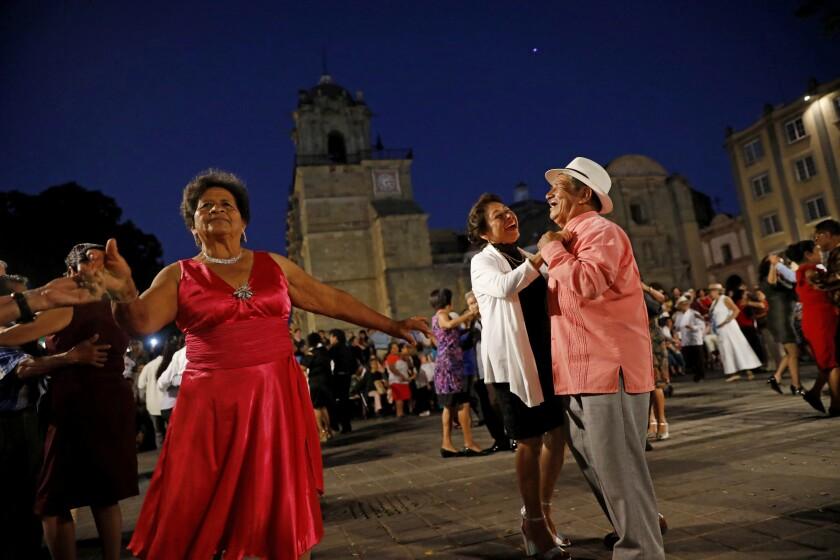 People dance to music played by Marimba del Gobierno de Estado de Oaxaca, in the zócalo in Oaxaca, Mexico.