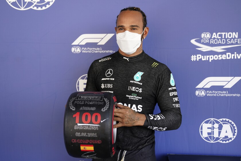 Mercedes driver Lewis Hamilton of Britain poses with a wheel-shaped award.