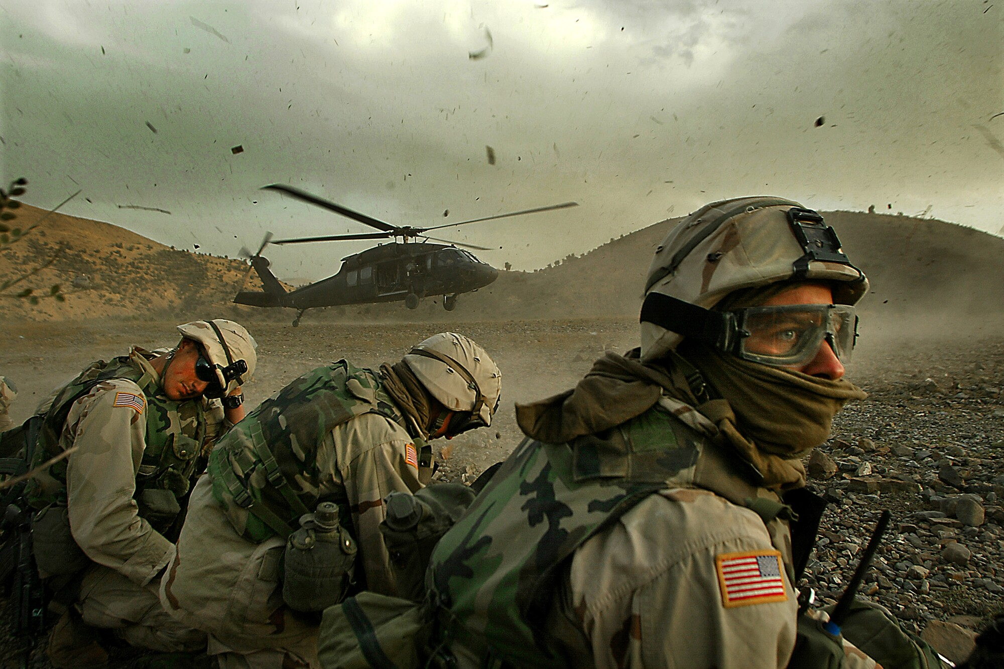 Soldiers turn their heads away from a landing helicopter kicking up dust and debris