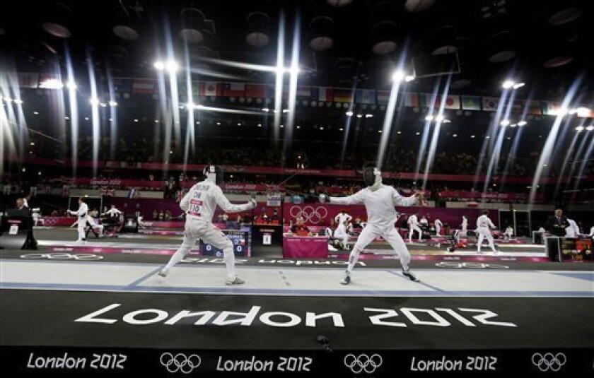 FILE - In this Saturday, Aug. 11, 2012 file photo, Cao Zhongrong of China, left, and Ondrej Polivka of the Czech Republic compete during the fencing section of the men's modern pentathlon at the 2012 Summer Olympics. (AP Photo/Kirsty Wigglesworth, File)